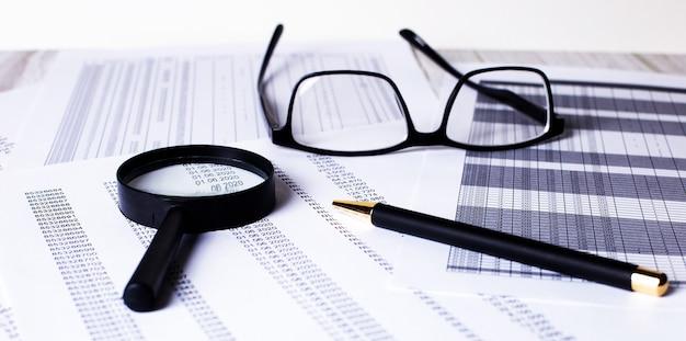 明るい木製のテーブルの上に、書類の山、虫眼鏡、ペン、黒いフレームの眼鏡が置かれています
