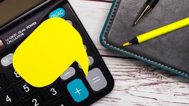 На светлом деревянном столе есть калькулятор, блокнот, ручка, желтый карандаш и желтая карточка с местом для вставки текста. бизнес-концепция. шаблон