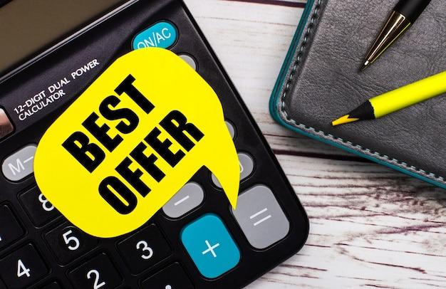 На светлом деревянном столе есть калькулятор, блокнот, ручка, желтый карандаш и желтая карточка с текстом best offer. бизнес-концепция.