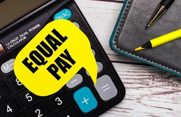 На светлом деревянном столе есть калькулятор, блокнот, ручка, желтый карандаш и желтая карточка с надписью equal pay. бизнес-концепция.