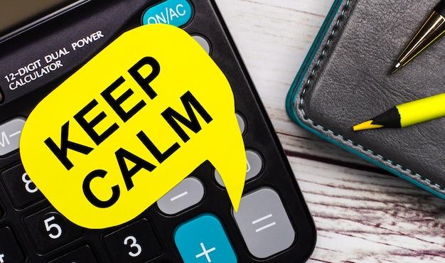 На светлом деревянном столе есть калькулятор, блокнот, ручка, желтый карандаш и желтая карточка с надписью «сохраните спокойствие». бизнес-концепция.