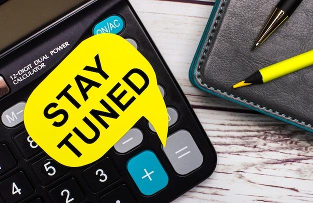 На светлом деревянном столе есть калькулятор, блокнот, ручка, желтый карандаш и желтая карточка с надписью stay tuned. бизнес-концепция.