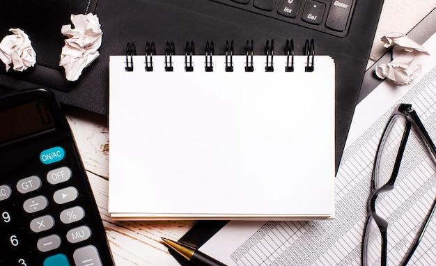 明るい木製のテーブルには、ラップトップ、電卓、ペン、黒いフレームのメガネ、テキストを挿入する場所のある白い空白のノートがあります。コピースペース
