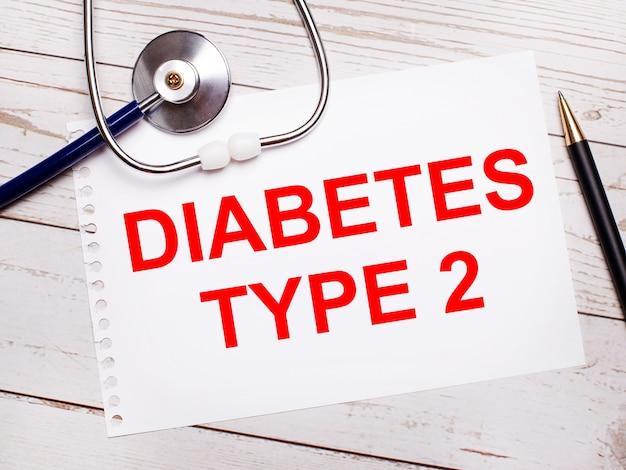 На светлом деревянном столе стетоскоп, ручка и лист бумаги с надписью «диабет тип 2». медицинская концепция.