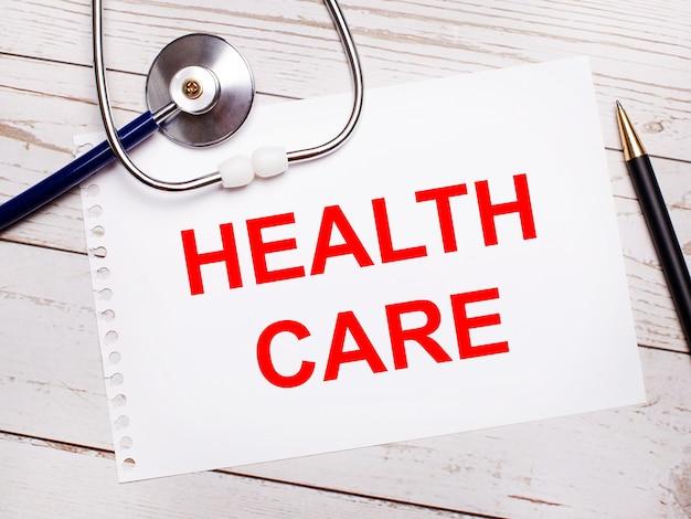 明るい木製のテーブルには、聴診器、ペン、そして「ヘルスケア」と書かれた一枚の紙があります。医療コンセプト