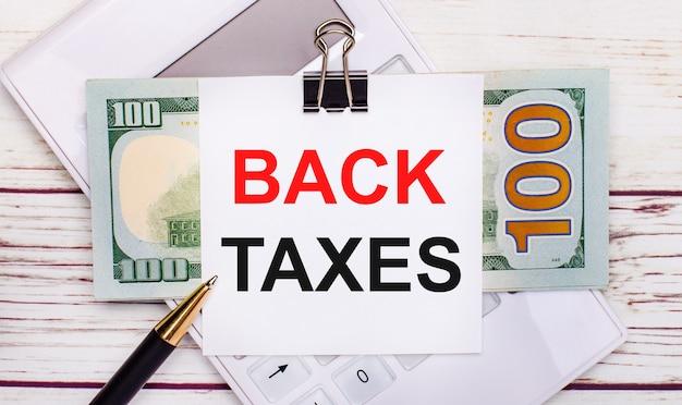На светлом деревянном столе белый калькулятор, ручка, счета и лист бумаги под черной канцелярской скрепкой с надписью налоги назад. бизнес-концепция