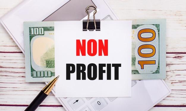 На светлом деревянном столе белый калькулятор, ручка, банкноты и лист бумаги под черной канцелярской скрепкой с надписью non profit. бизнес-концепция