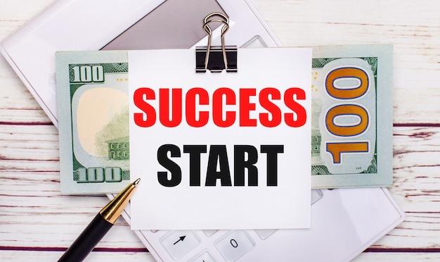 На светлом деревянном столе белый калькулятор, ручка, банкноты и лист бумаги под черной канцелярской скрепкой с надписью успех начала. бизнес-концепция