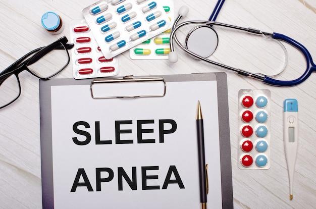 На светлом деревянном столе - бумага с надписью sleep apnea, стетоскоп, разноцветные пилюли, очки и ручка. медицинская концепция