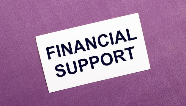 На сиреневом фоне белая карточка с надписью финансовая поддержка.