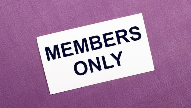 На сиреневом фоне белая карточка с надписью только для членов.