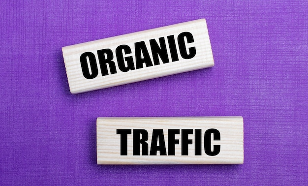 На сиреневом ярком фоне светлые деревянные блоки с надписью organic traffic.