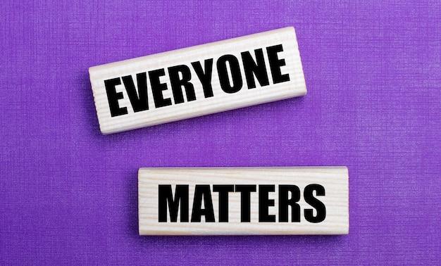 薄紫色の明るい表面に、「みんなが重要」というテキストが書かれた明るい木製のブロック