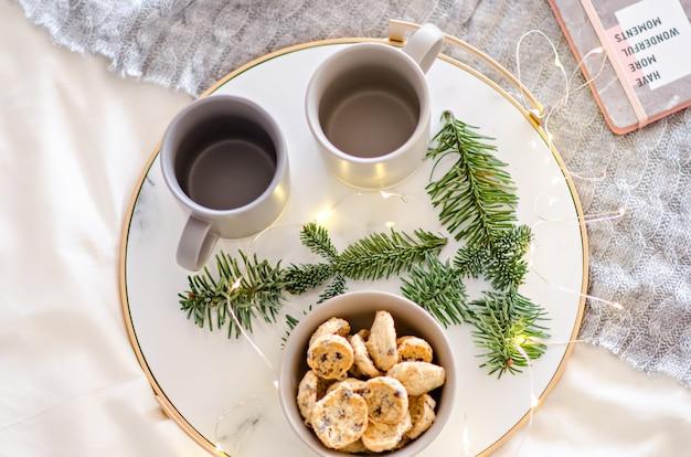 金の縁のある大理石のトレイには、2つの灰色のお茶とチョコレートのジンジャーブレッドクッキーがあります。サンタクロースの御馳走。花輪のあるクリスマスツリーの枝が年賀状を飾ります。コピースペース