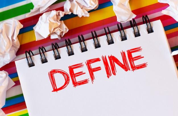 На разноцветном полосатом фоне белые бумажки и белый блокнот с красной надписью define.