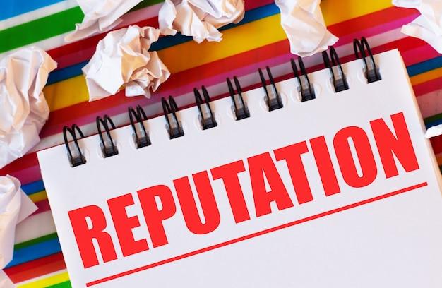 На разноцветном полосатом фоне белые бумажки и белый блокнот с красной надписью reputation.