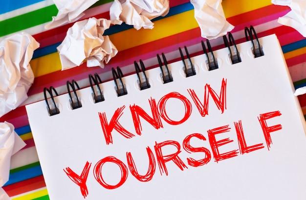 マルチカラーの縞模様の表面には、白い紙と赤いノートがあります。knowyourself