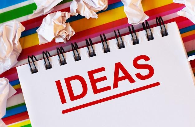 На разноцветном полосатом фоне белые бумажки и белый блокнот с красной надписью ideas.