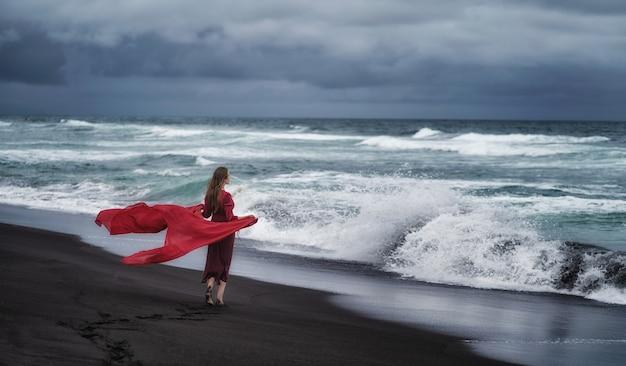 На тихоокеанском пляже камчатки в пасмурную погоду девушка с распущенными волосами в длинном приталенном красном платье.