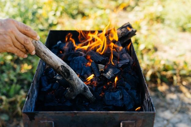 자연의 피크닉에서 한 남자가 바베큐에 불을 붙입니다.