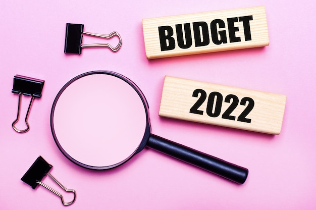 ピンクの背景に、拡大鏡、黒いペーパークリップ、テキストbudget2022の木製ブロック。ビジネスコンセプト