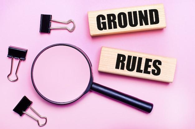 На розовом фоне лупа, черные канцелярские скрепки и деревянные блоки с текстом правила земли. бизнес-концепция