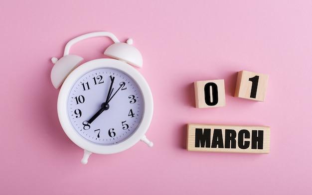 ピンクの背景に、白い目覚まし時計と3月1日の日付の木製の立方体