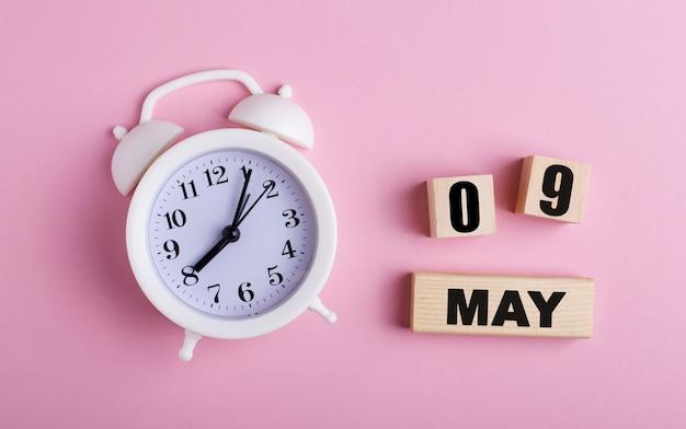 ピンクの背景に、白い目覚まし時計と5月9日の日付の木製の立方体。