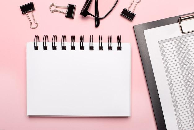 ピンクの背景に、レポート、黒いペーパークリップ、メガネ、テキストを挿入する場所のある空白のノートブック