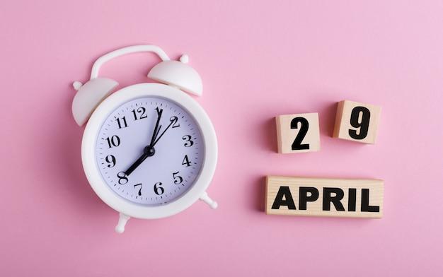 ピンクの表面に、白い目覚まし時計と4月29日付けの木製の立方体