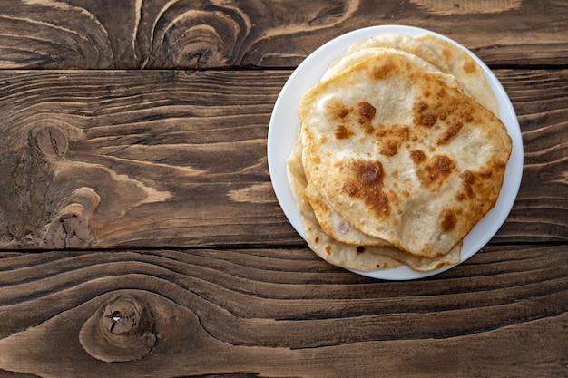 На тарелке лежат жареные хлебные лепешки, вид дерева текстурированный стол сверху. со свободным текстом, копией пространства,