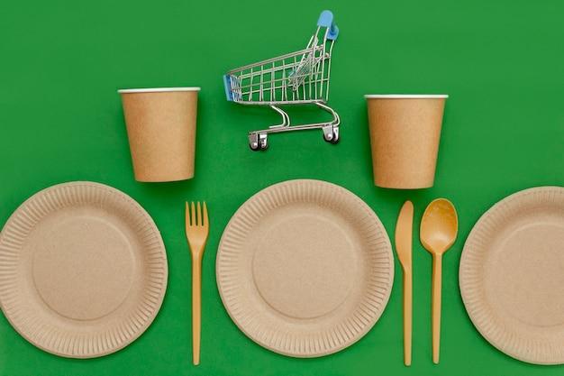 재활용 가능한 접시에는 작은 쇼핑 카트가 있고 포크, 스푼, 나이프, 컵 옆에 녹색 배경이 있습니다. 주방 용품은 테이블에 제공됩니다. 평면도. 미니멀리스트 스타일. 공간을 복사합니다.