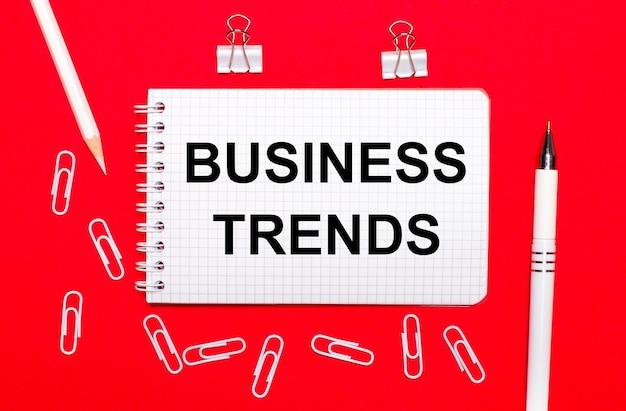 На красном фоне белая ручка, белые канцелярские скрепки, белый карандаш и блокнот с текстом деловые тенденции.