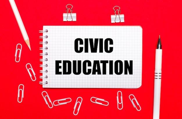 赤い背景に、白いペン、白いペーパークリップ、白い鉛筆、civiceducationというテキストのノート。上から見る