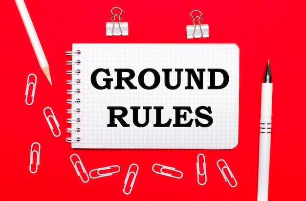 赤い背景に、白いペン、白いペーパークリップ、白い鉛筆、groundrulesというテキストのノートがあります。上から見る