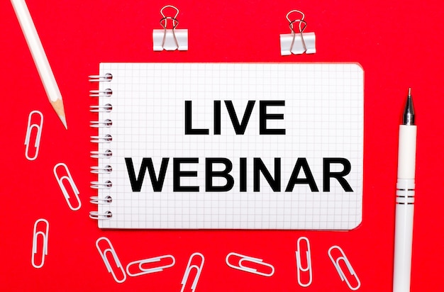 На красном фоне белая ручка, белые скрепки, белый карандаш и блокнот с текстом live webinar. вид сверху
