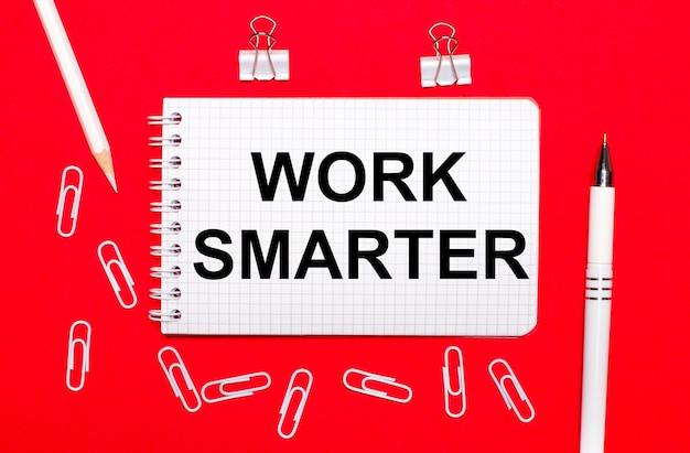 빨간색 배경에는 흰색 펜, 흰색 종이 클립, 흰색 연필 및 work smarter라는 텍스트가있는 노트북이 있습니다. 위에서보기