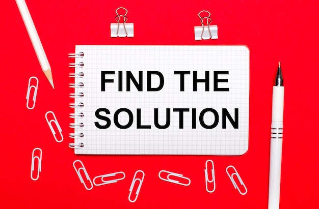 赤い表面に、白いペン、白いペーパークリップ、白い鉛筆、「ソリューションを探す」というテキストが書かれたノート