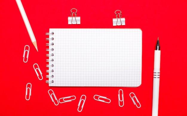 빨간색 테이블, 흰색 펜, 흰색 종이 클립, 흰색 연필 및 빈 노트. 복사 공간이있는 평면도
