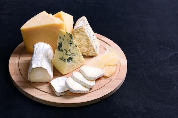 На круглой деревянной доске четыре вида сыра - твердый, мягкий, с голубой и белой плесенью.