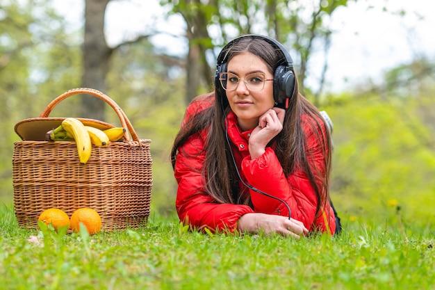 晴れた春の日に、公園の芝生の上のピクニックバスケットの隣に横たわって音楽を聴く眼鏡の若い女性