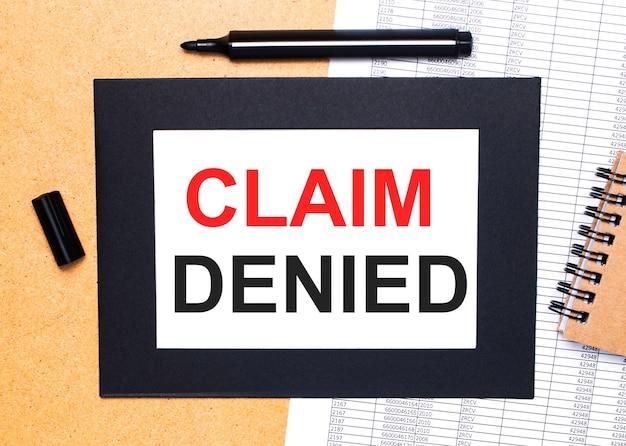 На столе маркер, блокнот и лист бумаги в черной рамке с текстом «претензия отказана».