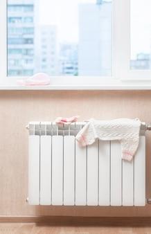 На теплом радиаторе сохнет детская одежда.
