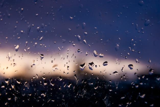 На мокром стекле вечером хорошо видны капли воды