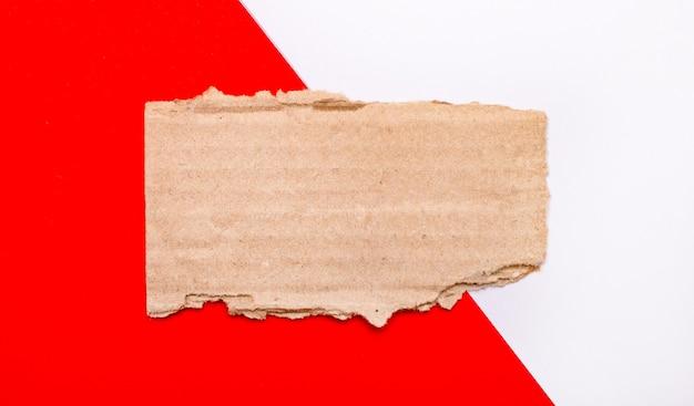 白と赤の背景に、テキストやイラストの場所と茶色の破れた段ボール。レンプレート