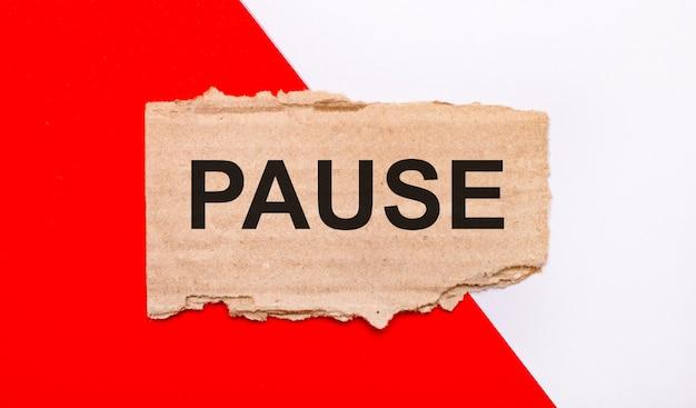 白と赤の背景に、pauseというテキストが付いた茶色の破れた段ボール