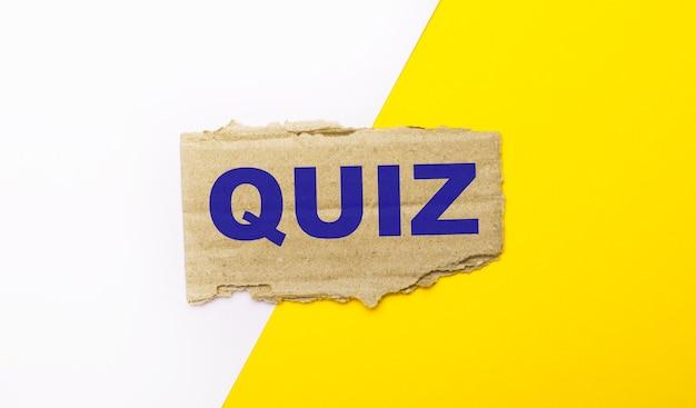 白と黄色の背景に、クイズのテキストが付いた茶色の破れた段ボール
