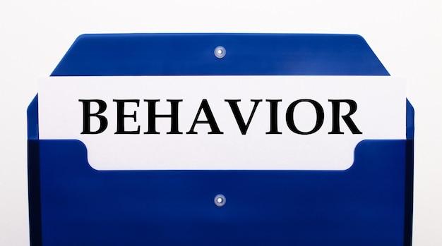 На белом фоне синяя папка для бумаг. в папке лежит листок со словом поведение.