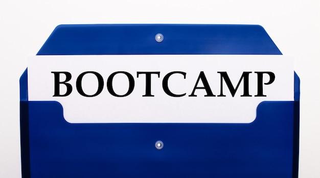 白い背景の上に、紙のための青いフォルダー。フォルダには、bootcampという単語が書かれた1枚の紙があります