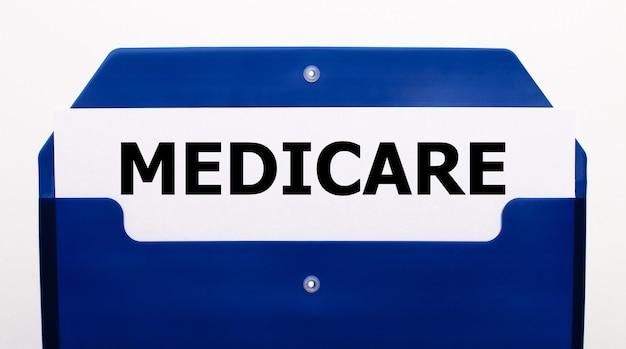 На белом фоне синяя папка для бумаг. в папке лежит лист бумаги со словом medicare.